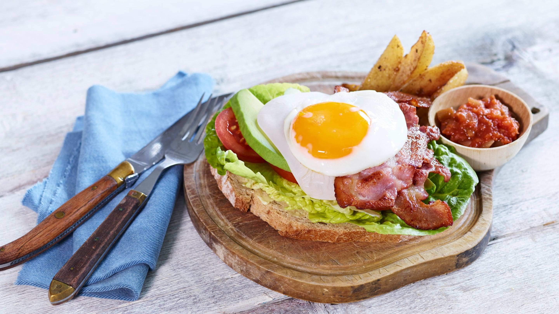 Sandwich med stekt egg, bacon, salat og kalkunpålegg